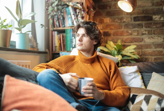 Handsome man sitting on the couch at home, drinking a cup of tea or coffee