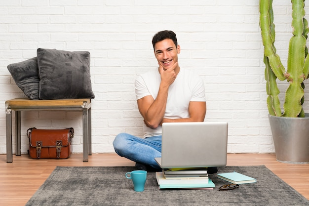 Handsome man sitting on the floor with his laptop laughing