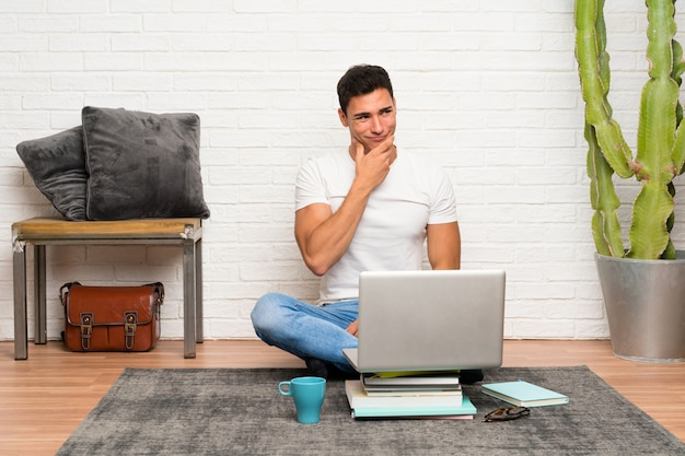 Handsome man sitting on the floor with his laptop thinking an idea