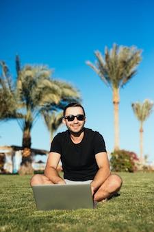 Bell'uomo seduto sull'erba e utilizzando il computer portatile.
