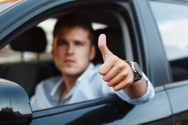 車に座って親指を立ててハンサムな男