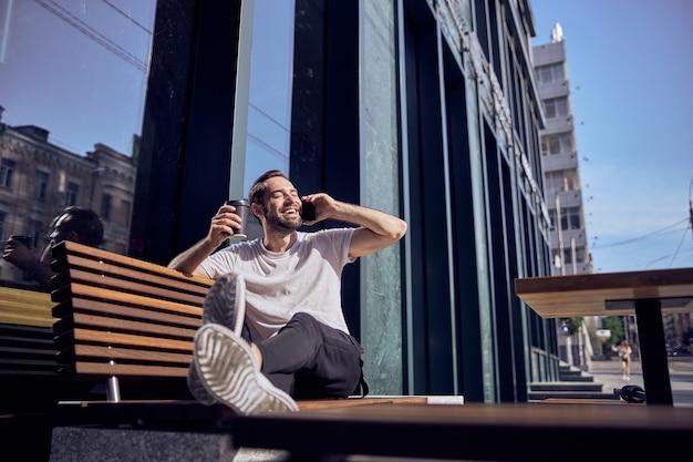 스마트 폰 및 커피 야외 벤치에 앉아 잘 생긴 남자