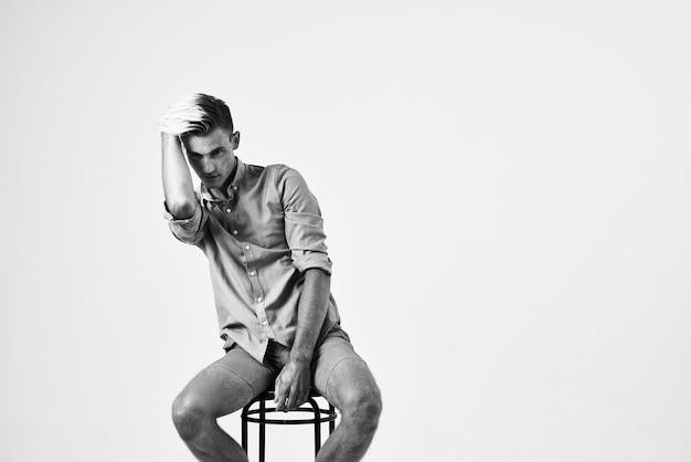 椅子に座っているハンサムな男ファッショナブルな髪型自信のポーズ