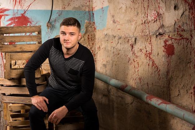 할로윈 공포 컨셉의 끔찍한 지하실에서 빈 포장 상자에 앉아 있는 잘생긴 남자