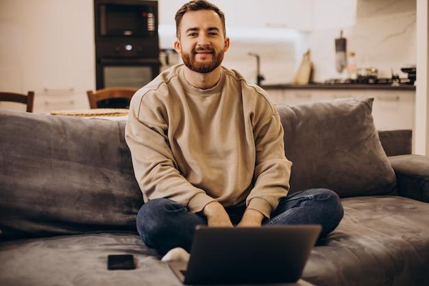 Красивый мужчина сидит на диване у себя дома и использует гаджеты