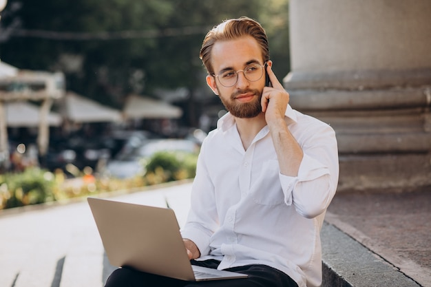 階段に座って、コンピューターで作業しているハンサムな男