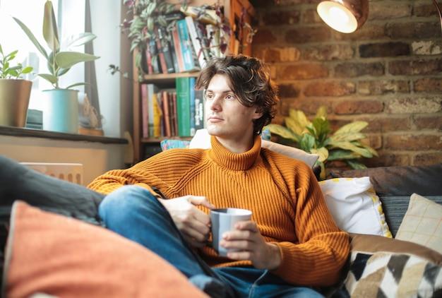 Красивый мужчина сидит на диване дома, пьет чашку чая или кофе