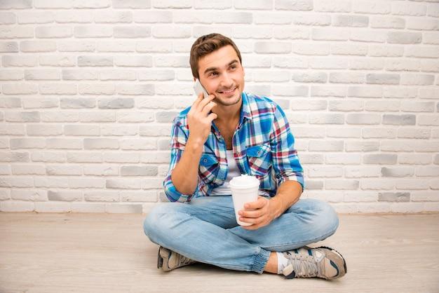 足を組んで床に座って電話を持っているハンサムな男