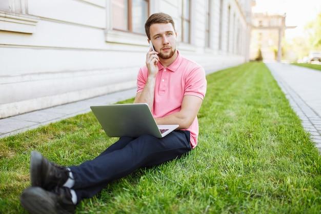 Красивый мужчина сидит на траве в городе с ноутбуком и разговаривает по телефону, поиск работы