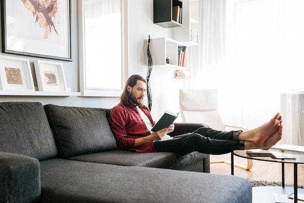 Handsome man sitting and reading book on sofa at home