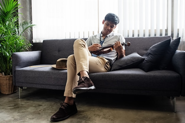 The handsome man sitting on sofa, holding violin in hand and pressing