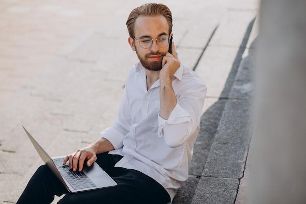 Bell'uomo seduto sulle scale e lavorando al computer Foto Gratuite