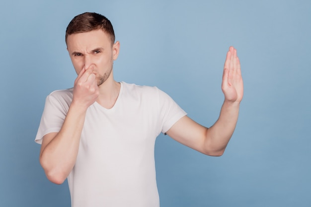 파란색 배경 위에 격리된 코에 손가락을 대고 냄새나고 역겨운 냄새를 풍기는 잘생긴 남자