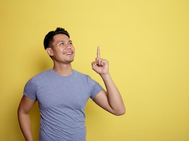 黄色の背景に分離されたハンサムな男の笑顔の物事のアイデア