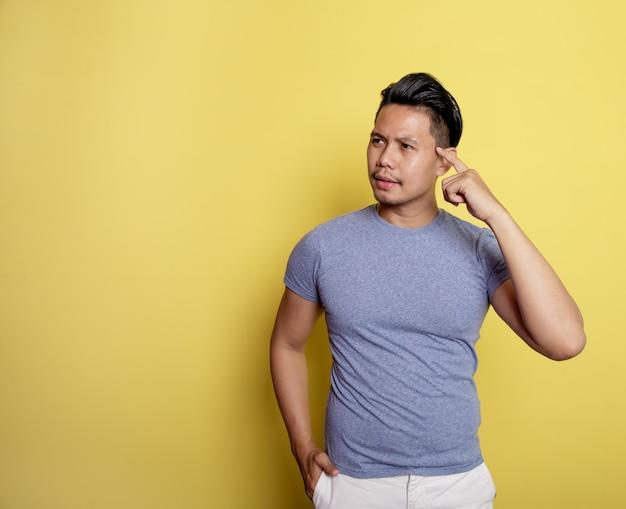 ハンサムな男は、黄色の背景で隔離の頭を保持して物事のアイデアを笑顔