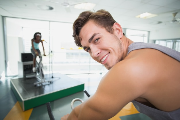Handsome man smiling at camera in spin class