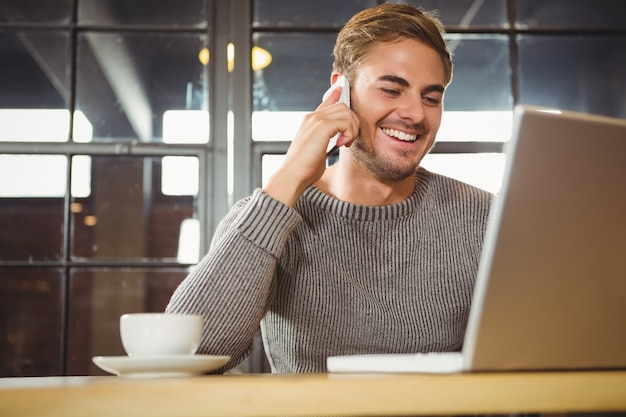 Handsome man smiling and phoning with smartphone