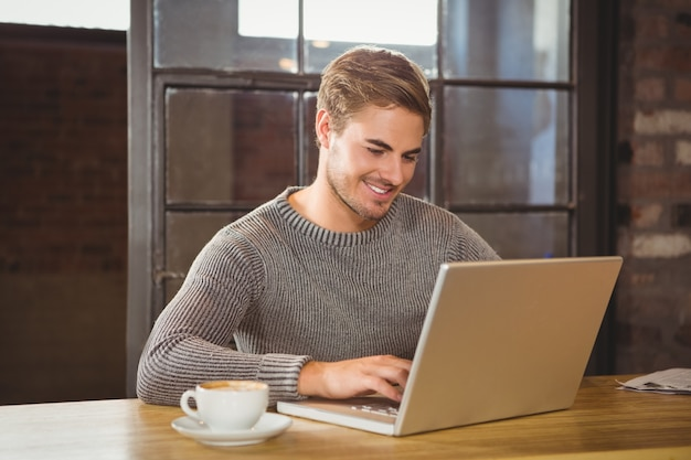 Handsome man smiling and typing on laptop