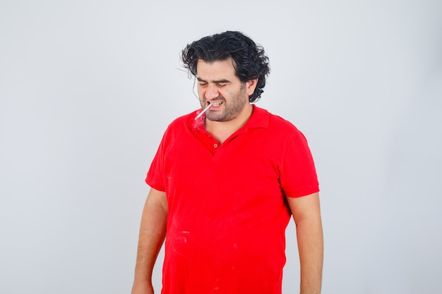 Handsome man smoking cigarette in red t-shirt and looking annoyed. front view.