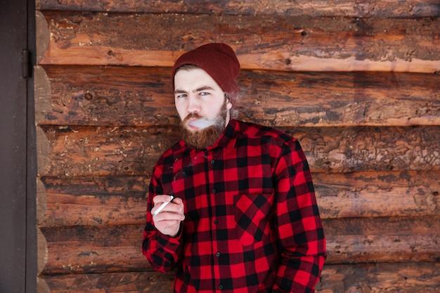 Красивый мужчина курит на деревянном доме Premium Фотографии