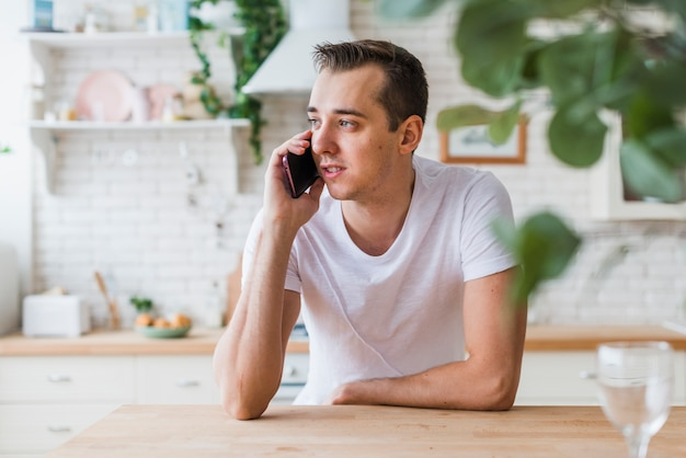 Handsome man speaking by phone in kitchen