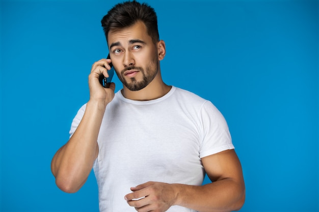 Handsome man speaks by phone and seems lost