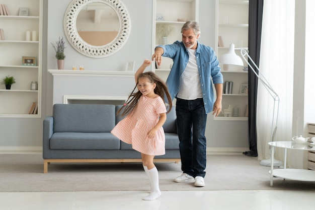 Handsome man spending time at home with his cute little daughter. happy father's day! dad and daughter.