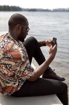 야외에서 시간을 보내고 현대적인 스마트폰을 사용하는 잘생긴 남자