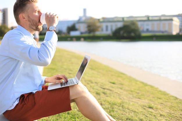 ベンチに座ってコーヒーを飲みながらラップトップコンピューターを使用して、街で屋外で時間を過ごすハンサムな男。