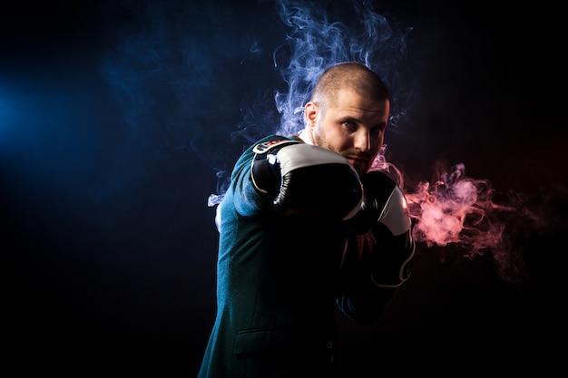 흰색 권투 장갑 권투와 빨간색과 파란색 연기의 반대를 다룰 준비가 잘 생긴 남자 운동가