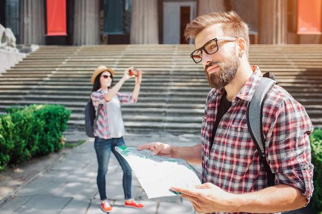 Красивый мужчина стоять снаружи и немного улыбнуться. он держит карту в руках. молодая женщина турист стоит на спине и фотографирует. они путешествуют.