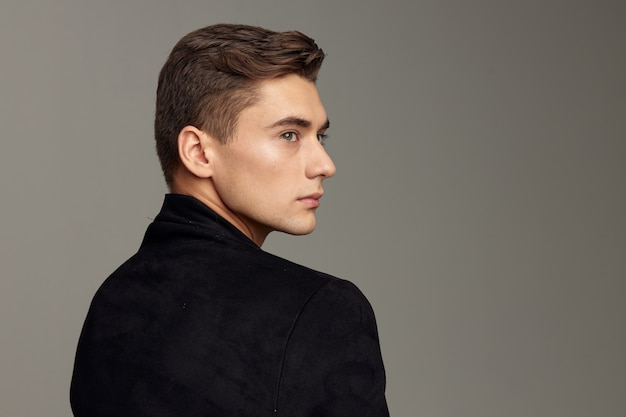 Handsome man standing back fashionable hairstyle posing cropped view. high quality photo