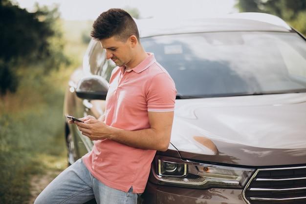 森の中の彼の車のそばに立っているハンサムな男