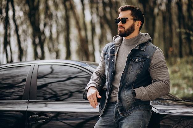 公園で車で立っているハンサムな男
