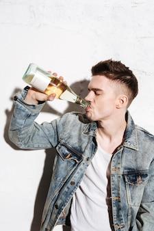 Uomo bello che sta sul pavimento che beve alcool