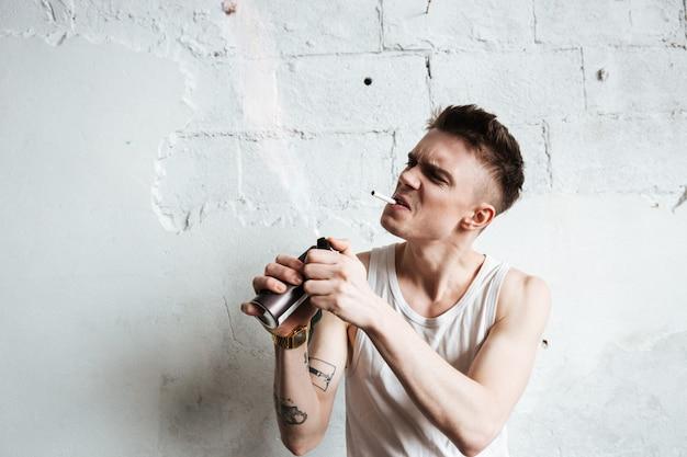 Uomo bello che sta sul pavimento con lo spruzzo e la sigaretta di gas