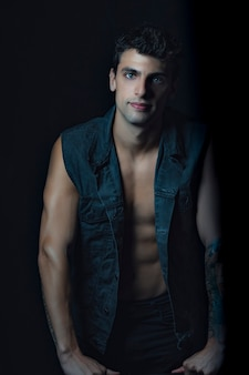 Handsome man standing looking at the camera wearing a jean vest and naked torso