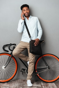 Handsome man standing near bicycle talking by phone.