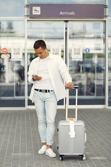 Красивый мужчина стоит возле аэропорта