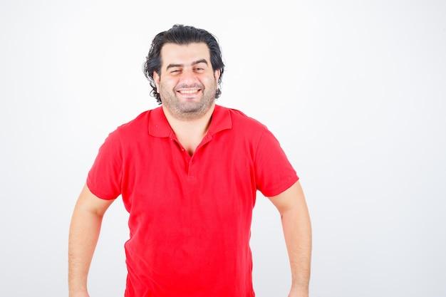 まっすぐ立って、赤いtシャツに笑みを浮かべて、陽気に見えるハンサムな男。正面図。