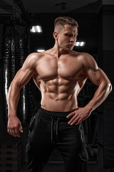 Handsome man standing strong in the gym and flexing muscles  muscular athletic bodybuilder fitness