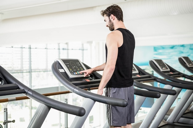 Handsome man standing on treadmill at the gym