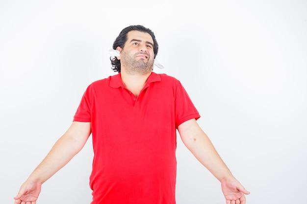 赤いtシャツの耳にナプキンを持って立って困惑しているハンサムな男、正面図。