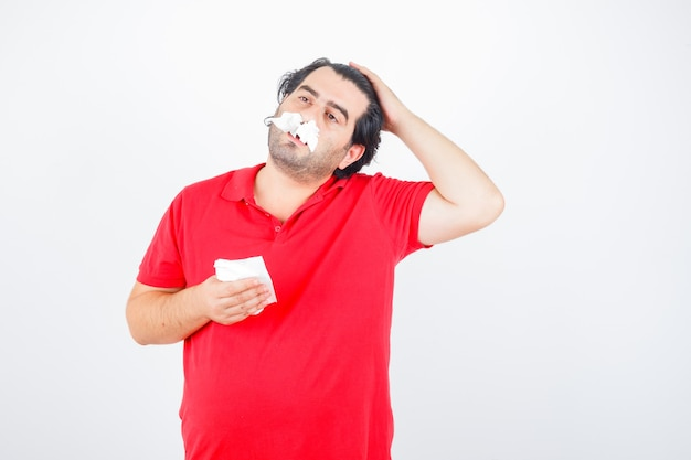 鼻の穴にナプキンを持って立って、ナプキンを手に持って、赤いtシャツを着て頭に手をつないで、疲れ果てているように見えるハンサムな男。正面図。