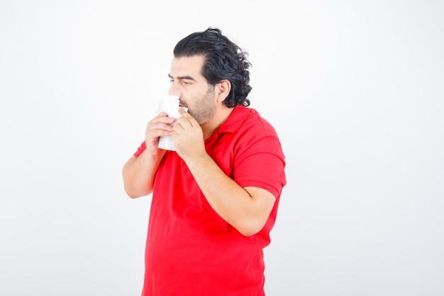 Handsome man standing with napkins in nostrils, holding napkin in hands in red t-shirt and looking exhausted. front view.
