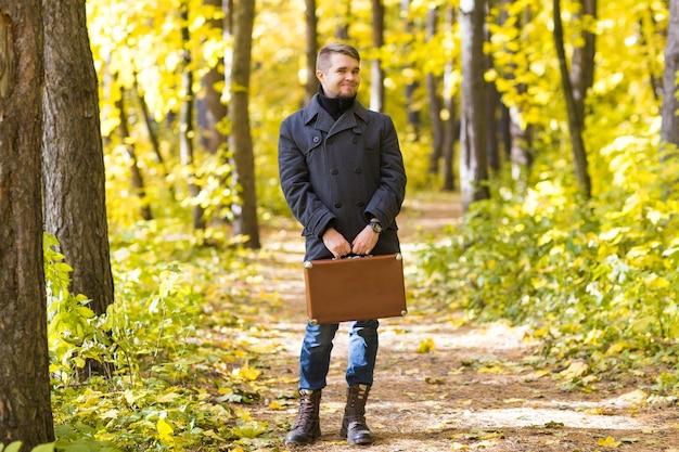 秋の公園でレトロなスーツケースと立っているハンサムな男