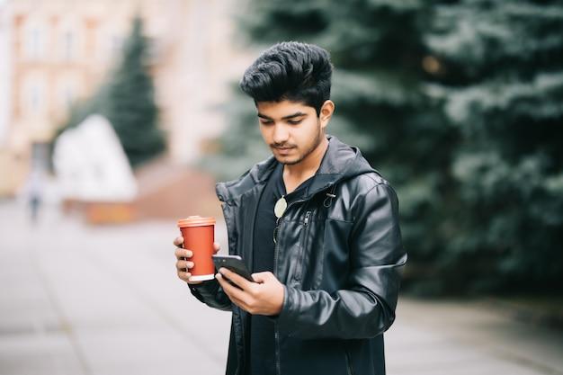 Studente bello dell'uomo con gli occhiali che parla con gli amici sul telefono cellulare che gode del caffè urbano mentre camminando sulla via