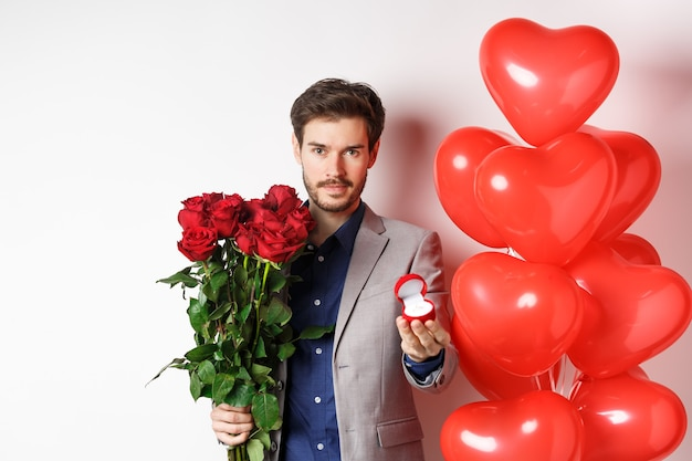 Handsome man in suit giving an engagement ring and bouquet of red roses, marry me on valentines day, standing with heart balloons on white background.