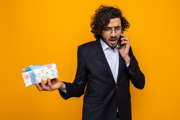 Bell'uomo in tuta che tiene presente con aria confusa mentre parla al telefono cellulare celebrando la giornata internazionale della donna l'8 marzo in piedi su sfondo arancione