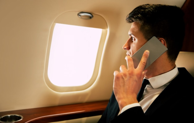 Handsome man in a suit is smiling and looking through the window while talking on the phone, flying business class with a laptop and a cup of coffee on it.